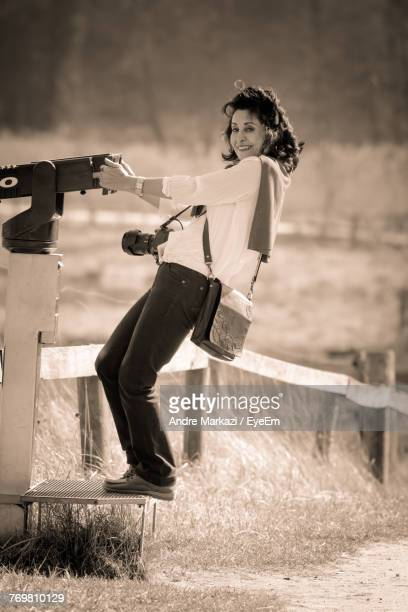 Woman By Coin-Operated Binoculars On Field