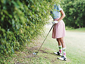 Woman by hedge leaning on golf club, head obscured by hedge, side view