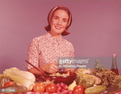 Woman by kitchen counter, tossing vegetables for salad. (Photo by H. Armstrong Roberts/Retrofile/Getty Images) : Foto de stock