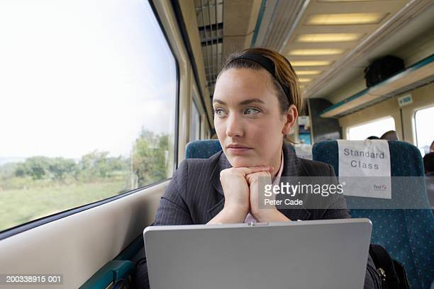 Woman by laptop looking out train window
