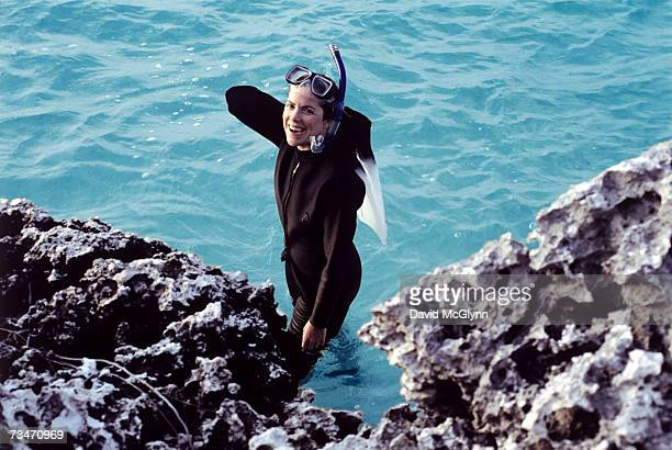 Woman by reef with snorkeling gear, in wetsuit, smiling, portrait