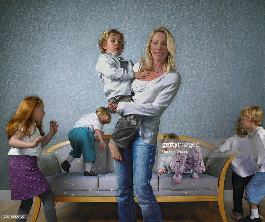 Woman by sofa surrounded by children (2-9), portrait : Stock Photo
