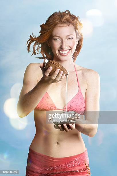 woman by the beach pouring out coconut milk