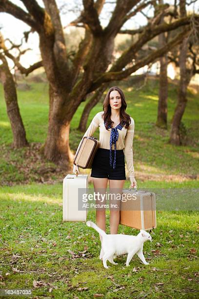 Woman by trees with vintage suitcases