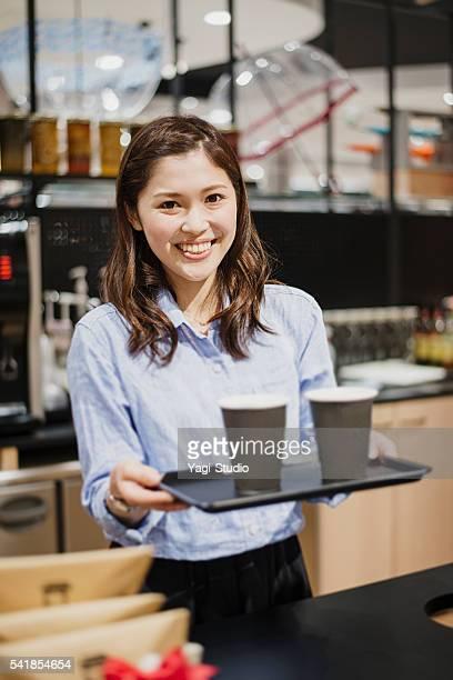 Femme debout devant le café employé de comptoir