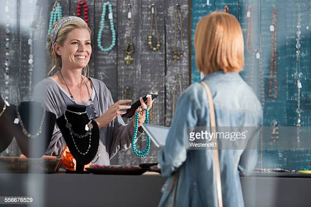 Woman calculating a price for a necklace