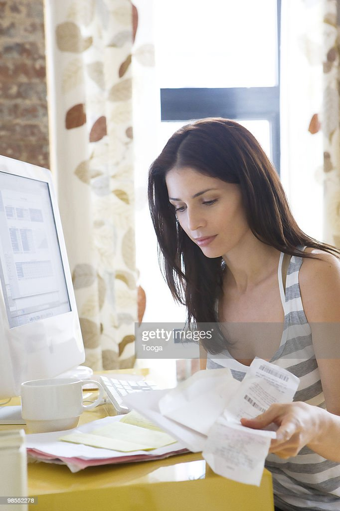 Woman calculating receipts at home : Stock Photo