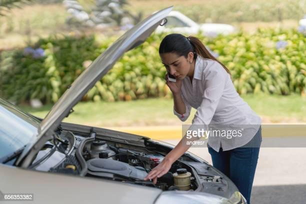 Femme appelant son assurance après une panne de voiture