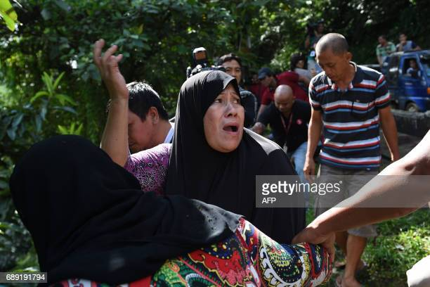 A woman calls out to her relatives after identifying bodies dumped off a cliff along the highway leading to Marawi on the southern island of Mindanao...