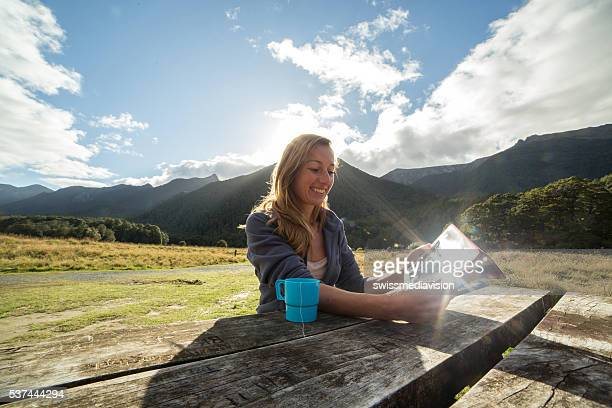 Woman camping in nature, uses a digital tablet