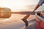 Woman canoeing at sunset on Jackfish Lake, Manitoba.
