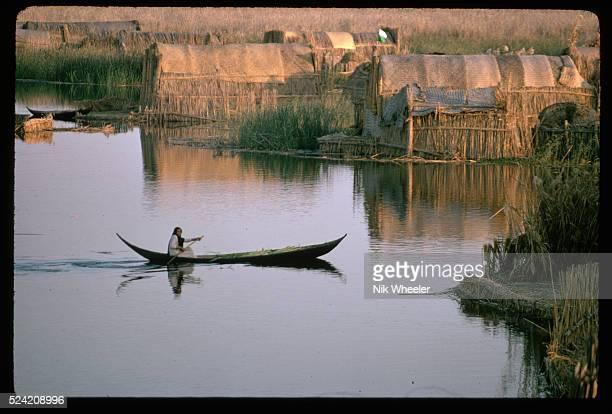 Woman Canoeing Through Marsh Arab Village