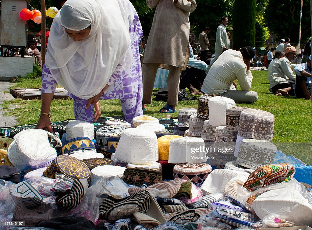 A woman cap seller arranges caps as muslims wait to offer prayers on the first Friday of holy month of Ramadan on July 12, 2013 in Srinagar, the summer capital of Indian administered Kashmir, India. Ramadan is the ninth month of Islamic lunar calendar, during which Muslims believe the Quran was given to Prophet Muhammad. Muslims across the globe refrain from eating, drinking and sex from dawn to dusk during the month. Besides spending more time praying, donating alms is mandatory. Every Muslim has to give 2.5 per cent of their wealth and assets, in excess of what is required, to the poor.
