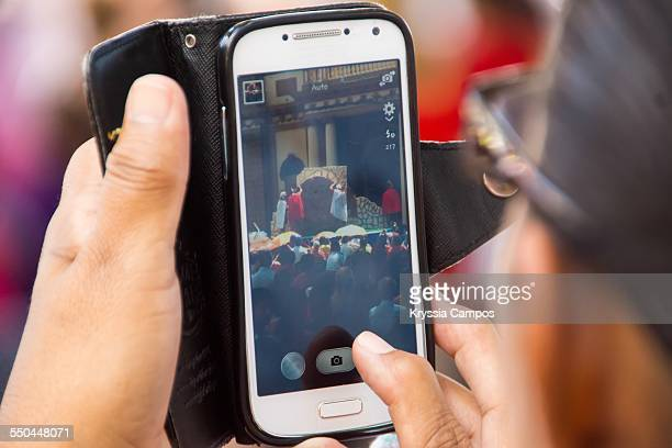 Woman captures a shot of the bibles scenes played by actors during the Good Friday procession in Naranjo Costa Rica