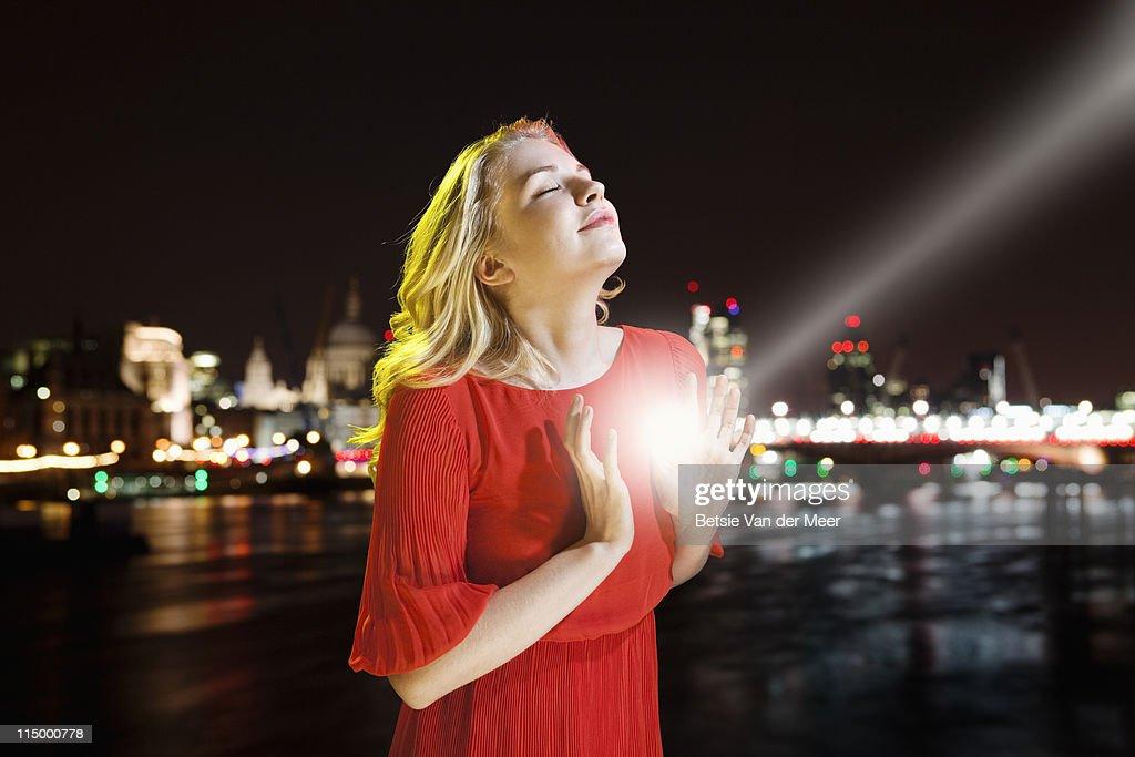 Woman capturing lightbeam between hands. : Stock Photo