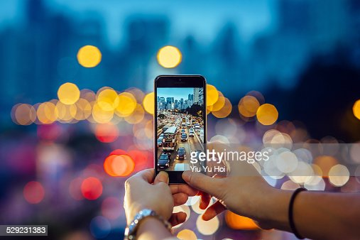 Woman capturing the busy traffic with smartphone