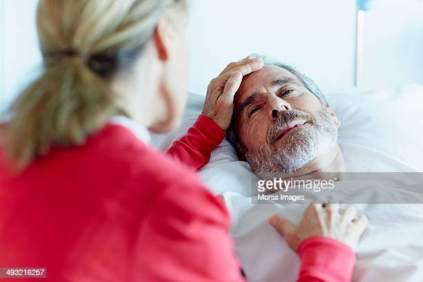 Woman caressing ill man in hospital ward