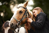 Woman caring for horse.