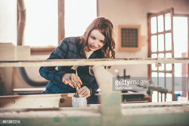 Woman carpenter inspecting freshly painted wood