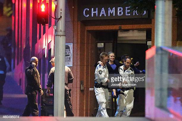A woman carried out by police from the Lindt Cafe Martin Place following a hostage standoff on December 16 2014 in Sydney Australia Police stormed...