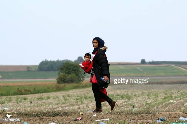 A woman carries a baby as migrants and asylum seekers walk through a field near the western Serbian town of Sid toward the border between Serbia and...