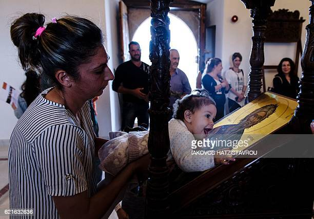 A woman carries a baby as she hugs an icon of the Apostle St Andrew at the newlyrestored Apostolos Andreas Monastery at Rizokarpaso a town in the...