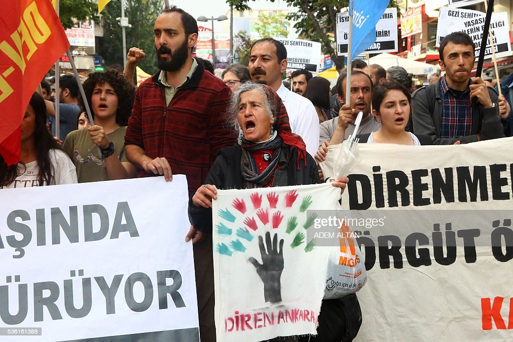 A woman carries a banner on May 31, 2016 in Ankara during a demonstration commemorating the third anniversary of the start of the Gezi Park protests. The Gezi Park protests which began in May 2013, were sparked by the heavy-handed eviction of demonstrators staging a sit-in protest against the redevelopment of the area and grew into often violent clashes with police as people demonstrated against much broader issues concerning perceived infringements of civil rights. / AFP / ADEM