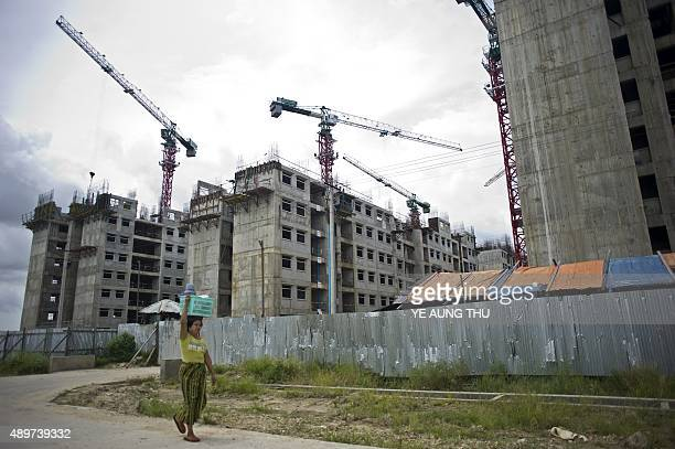A woman carries a basket as she walks past a low cost housing construction site on the outskirts of Yangon on September 24 2015 Plans to build a...