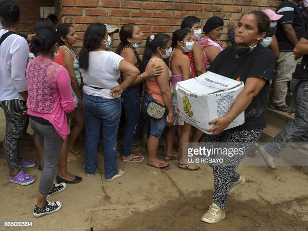 A woman carries a box with aid for people displaced by the floods in Mocoa Putumayo department southern Colombia on April 5 2017 A state of economic...