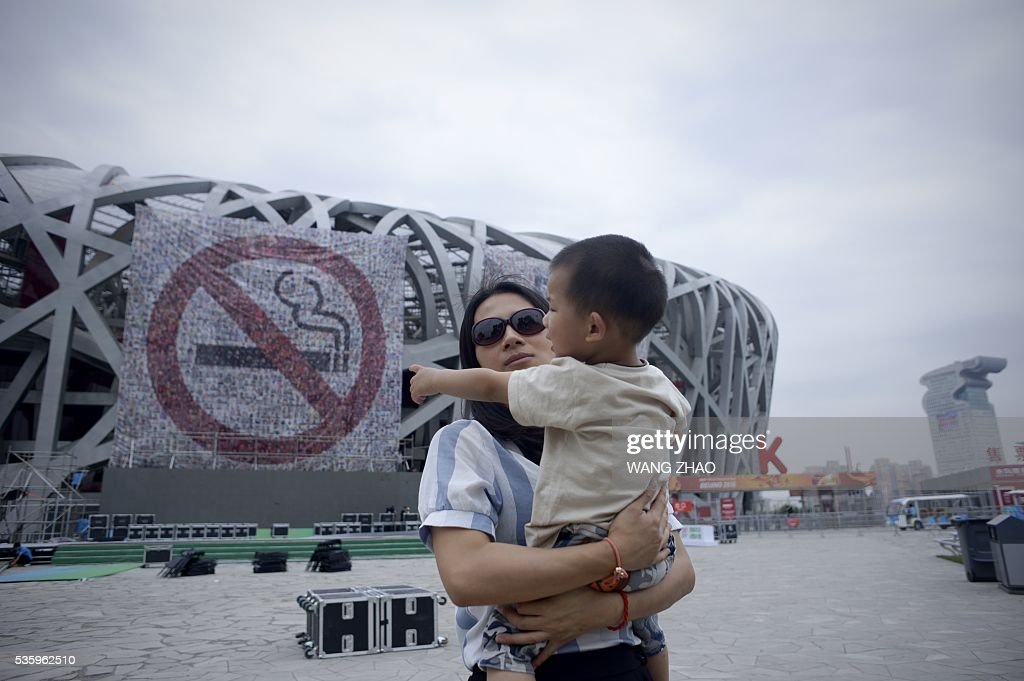 A woman carries a boy as she walks past a giant poster for World No Tobacco Day at the National Olympic Stadium or 'Birds Nest' in Beijing on May 31, 2016. May 31 is observed as World No Tobacco Day, with the World Health Organisation (WHO) using 'Get Ready For Plain Packaging' as the slogan of this year's day. / AFP / WANG