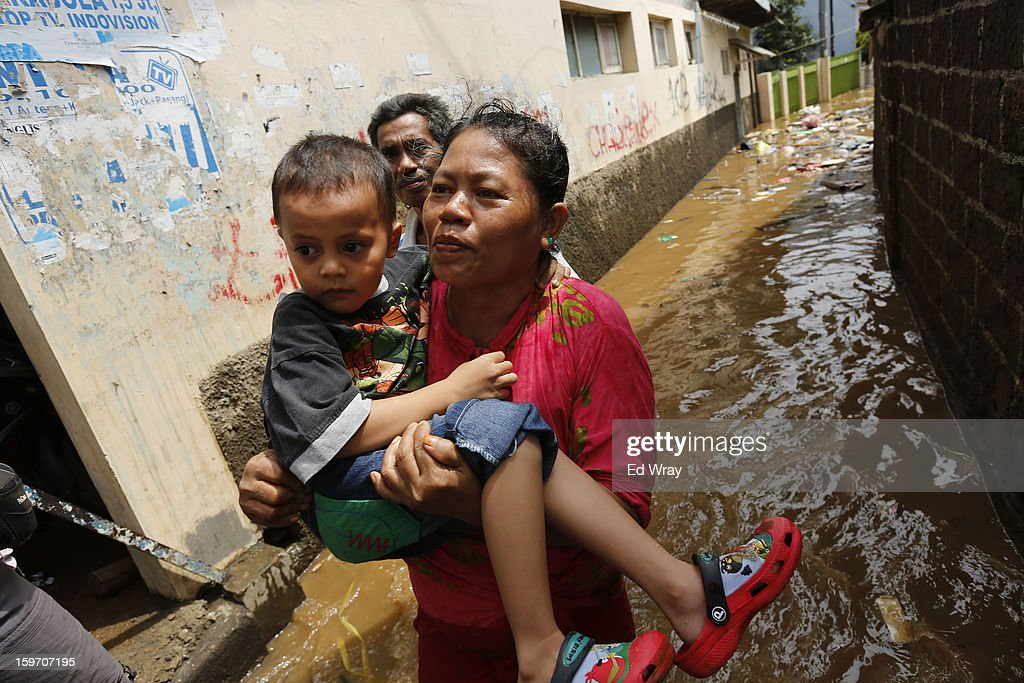 A woman carries a boy through floodwaters on January 19, 2013 in Jakarta, Indonesia. Floodwaters receded today after three days of heavy flooding which left thousands of people's homes underwater. According to Indonesian police the death toll has reached 15.