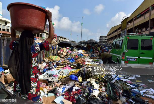 A woman carries a bucket next to a trash heap at the market of Adjame a working class neighbourhood of Abidjan on August 10 2017 / AFP PHOTO / ISSOUF...