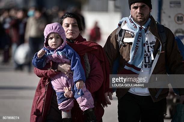 A woman carries a child as migrants and refugees arrive at the port of Piraeus near Athens from the Greek islands of Lesbos and Chios on February 1...
