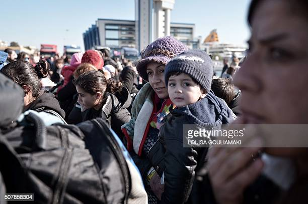 TOPSHOT A woman carries a child as migrants and refugees arrive at the port of Piraeus near Athens from the Greek islands of Lesbos and Chios on...