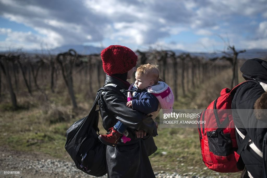 A woman carries a child as migrants and refugees cross the Greek-Macedonian border near the town of Gevgelija, on February 14, 2016. Dutch Foreign minister Bert Koenders on February 14 spent an hour in a Vinojug recipient center near Gevgelija talking with migrants, children, UNICEF and Red Cross representatives, police and others members that are taking care of migrants that are heading to the EU from devastated homes in Syria, Afghanistan and Iraq. / AFP / Robert ATANASOVSKI