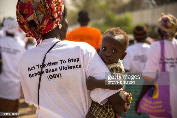 A woman carries a child as she joins others from more than forty South Sudanese womens organizations as they march through the city to express the...