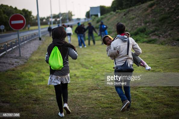 A woman carries a child as they walk towards the Eurotunnel terminal in Coquelles on July 31 2015 in Calais France Hundreds of migrants are...