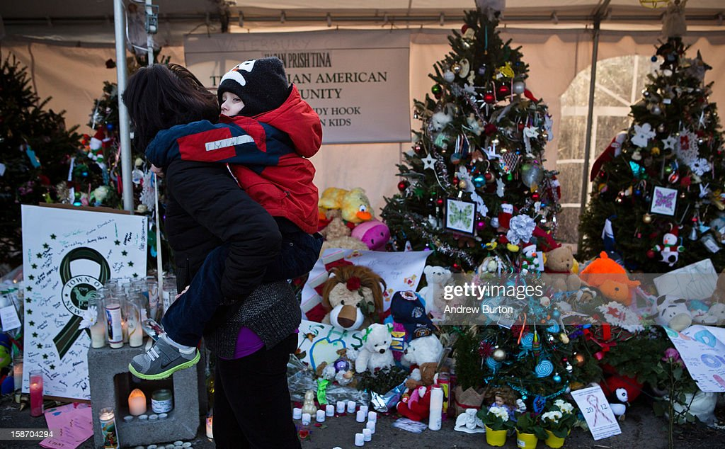 A woman carries a child on her back while observing a memorial for those killed in the school shooting at Sandy Hook Elementary School on December 24, 2012 in Newtown, Connecticut. Donations and letters are pouring in from across the country as the town tries to recover from the massacre.