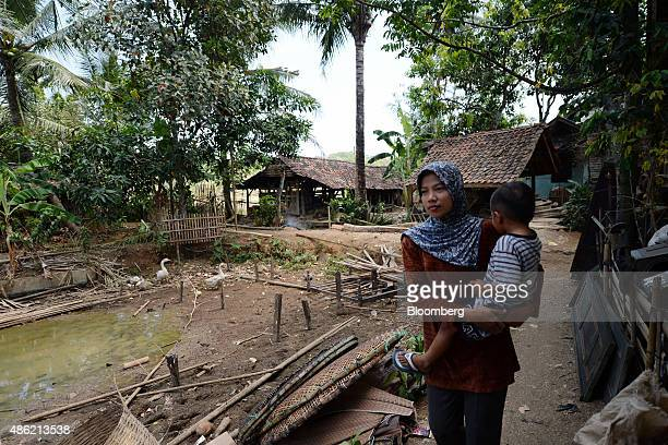 A woman carries a child past the site of a dismantled house in a village in West Java Indonesia on Tuesday Sept 1 2015 Indonesian President Joko...
