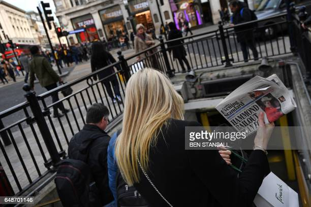 A woman carries a copy of the Evening Standard newspaper with its main headline referring to British Chancellor of the Exchequer Philip Hammond's...