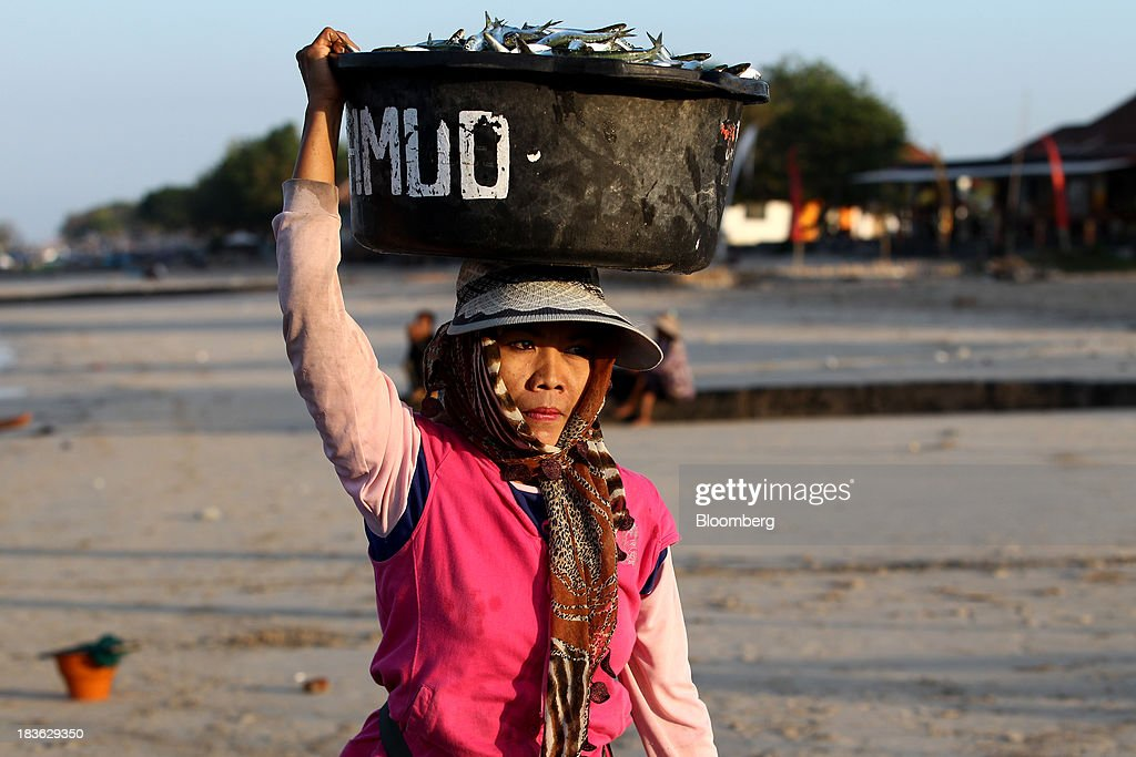 A woman carries a crate of fish on her head at Kedonganan beach in Jimbaran, Bali, Indonesia, on Saturday, Oct. 5, 2013. Indonesia's central bank kept its key interest rate unchanged after its most aggressive tightening cycle in almost eight years as inflation pressure eased. Photographer: SeongJoon Cho/Bloomberg via Getty Images