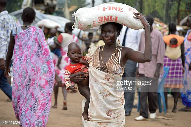 A woman carries a flour sack during a food distribution by the Catholic Church to refugees and displaced people in Juba on August 30 2014 Wartorn...