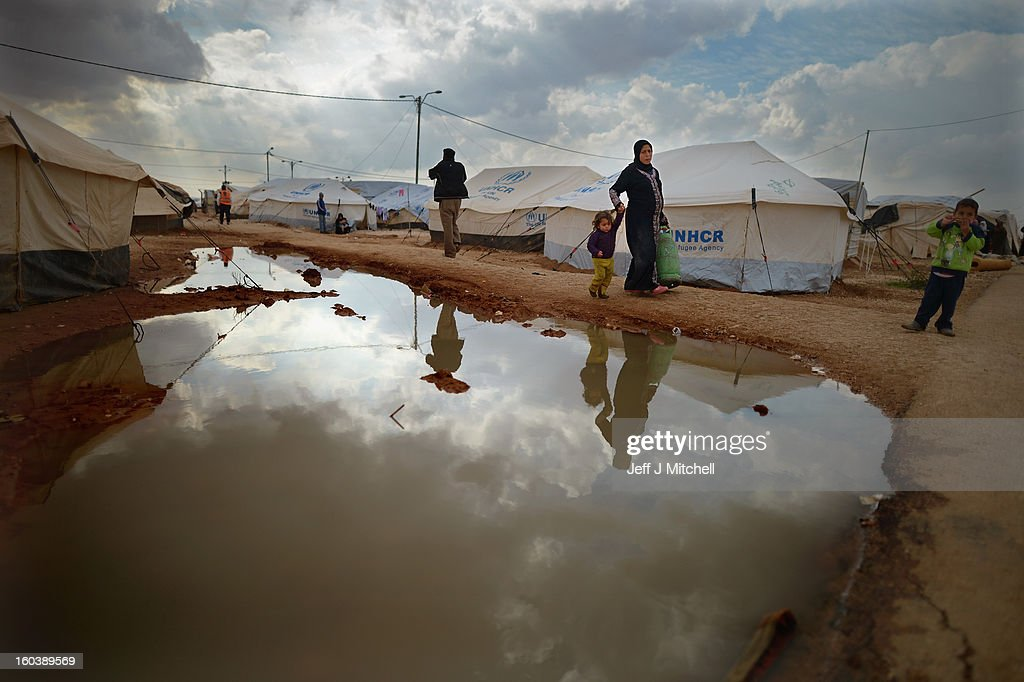ZA'ATARI JORDAN JANUARY 30 A woman carries a gas canister as Syrian refugees go about their daily business in the Za'atari refugee camp on January 30...