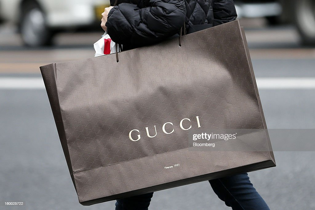 A woman carries a Gucci shopping bag in the Ginza district of Tokyo, Japan, on Friday, Jan. 25, 2013. Japan's consumer prices fell for the seventh time in eight months, underscoring the risk that the central bank may struggle to reach a 2 percent inflation target unless it implements new easing measures earlier than planned. Photographer: Kiyoshi Ota/Bloomberg via Getty Images