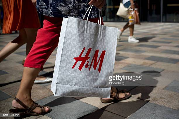 A woman carries a Hennes Mauritz AB shopping bag in the Sanlitun area of Beijing China on Monday Sept 8 2014 China is scheduled to release figures on...