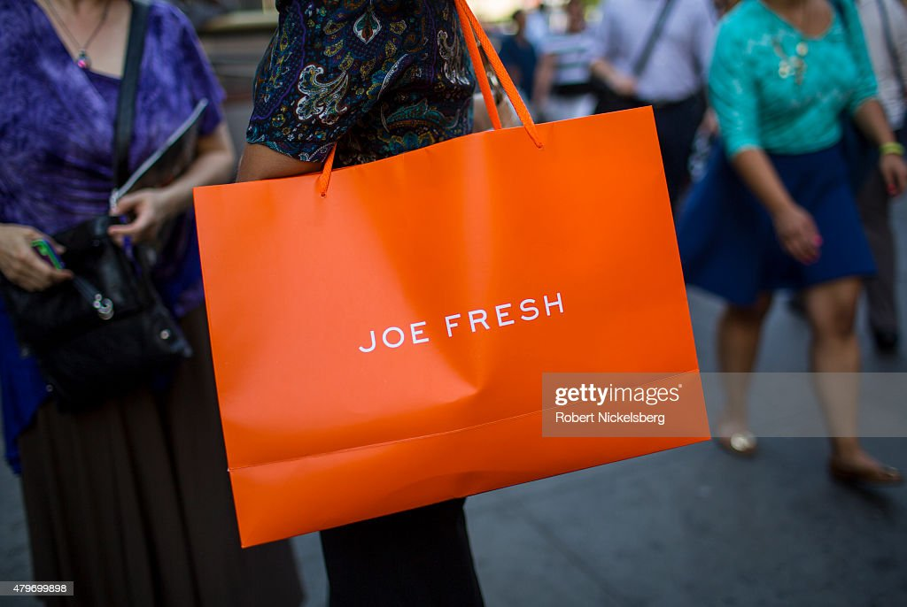 A woman carries a Joe Fresh bag May 27 2015 in the Manhattan borough of New York Joe Fresh is a trendy fashion and retail store created by designer...