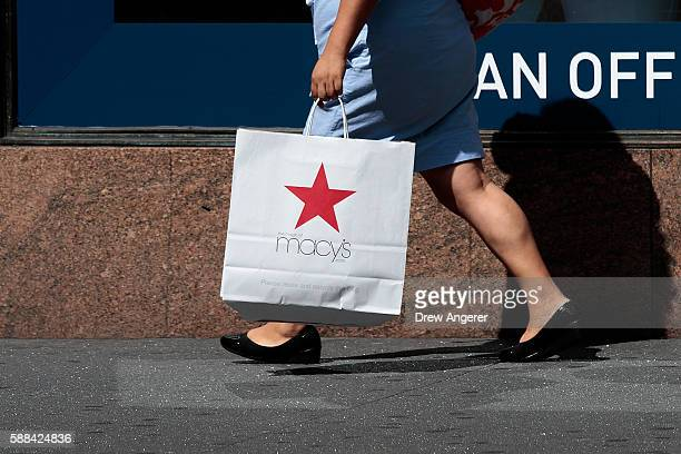 A woman carries a Macy's bag as the leaves Macy's flagship store in Herald Square August 11 2016 in New York City On Thursday Macy's announced plans...