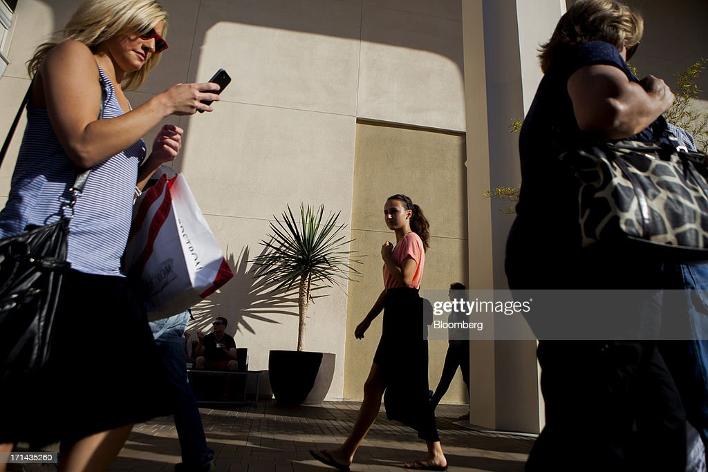 A woman carries a Nordstrom Inc. shopping bag while checking her phone at the Fashion Valley Mall in San Diego, California, U.S., on Saturday, June 22, 2013. The Bureau of Economic Analysis is schedule to release personal consumption figures on June 26. Photographer: Sam Hodgson/Bloomberg via Getty Images