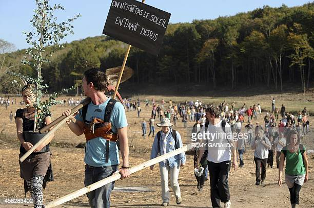 A woman carries a plant next to a man carriying tools and a placard reading 'You don't turn the sun off by shooting at it' as some 300 people take...