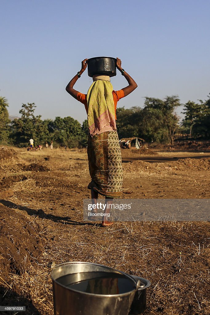 A woman carries a pot of water on her head at a brick manufacturer's in Kainad, Maharashtra, India, on Saturday, Dec. 21, 2013. The construction of 600,000 kilometers (373,000 miles) of country roads, addition of 327 million rural phone connections and a rise in literacy to record levels since Prime Minister Manmohan Singh took office in 2004 has helped double the growth rate of Indias food output. Photographer: Dhiraj Singh/Bloomberg via Getty Images